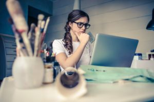 A woman with glasses looking at her laptop.