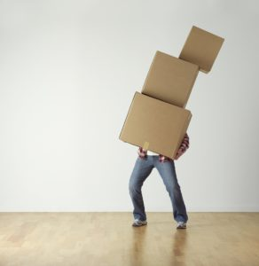 A man holding a bunch of comically large moving boxes. They're far bigger than his face.