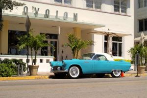A blue old-timer car parked in front of the hotel entrance.
