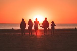 Happy people on the beach in the sunset - reasons to move to Miami