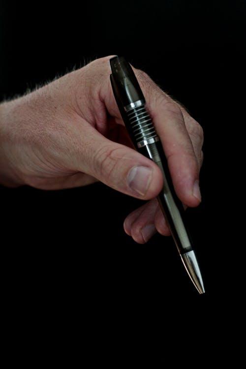 A hand holding a pen