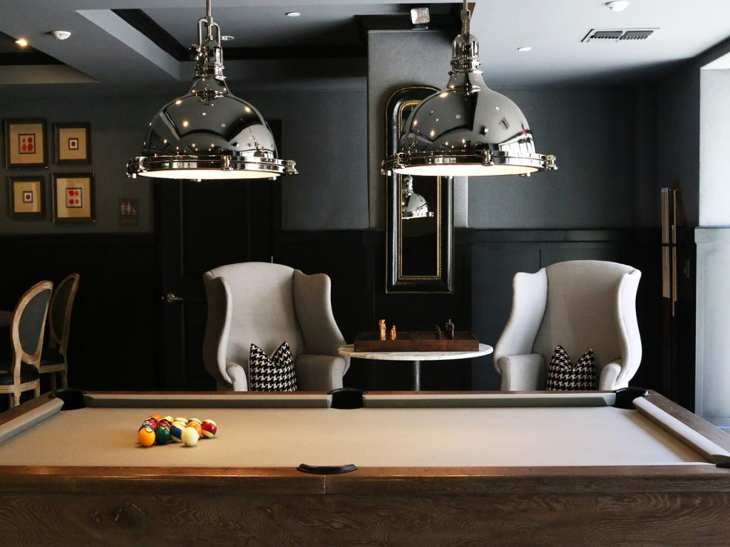 A modern living room with a brown pool table in the middle.