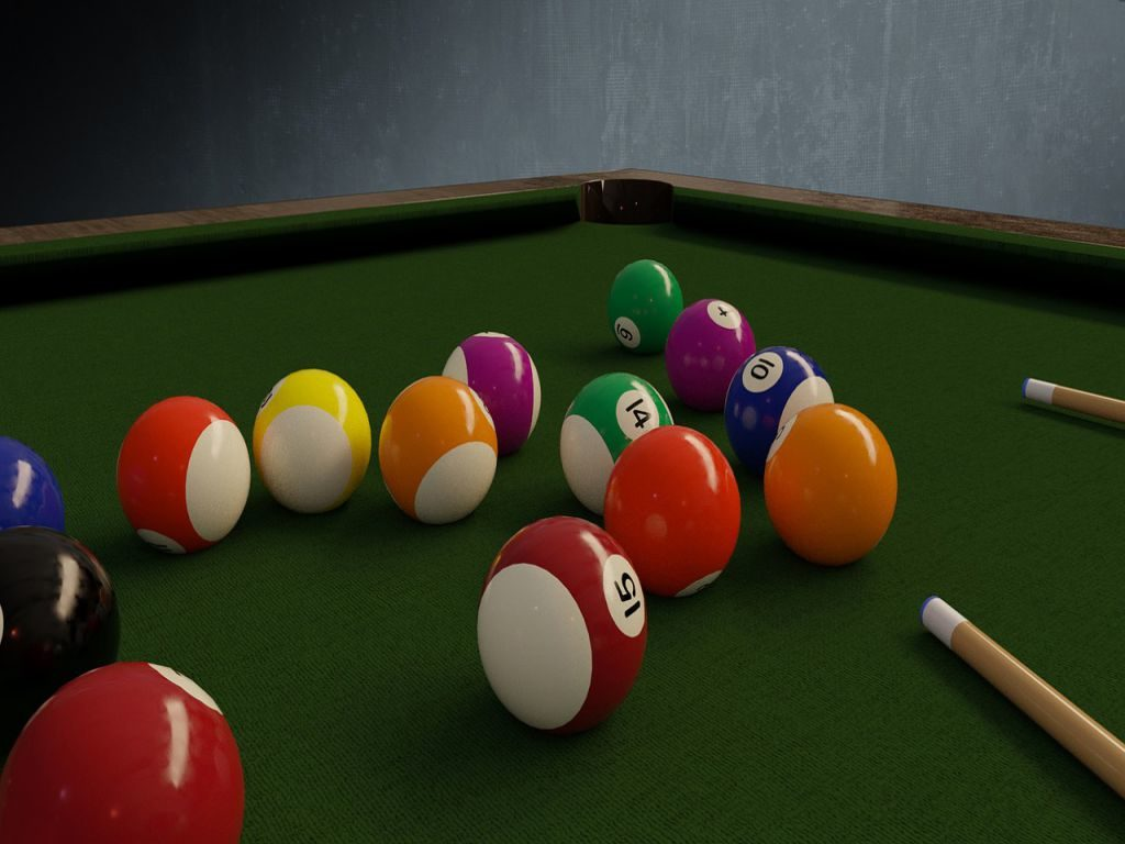 A view of billiard balls near a pocket liner on a table with green felt, which you will remove to disassemble a pool table.