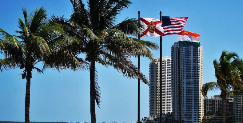 Florida and USA flags waving above hottest neighborhoods in Miami.