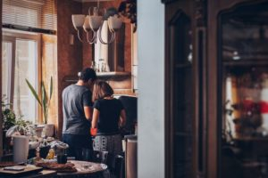 Couple cooking in the kitchen inside the house after moving in together in Miami