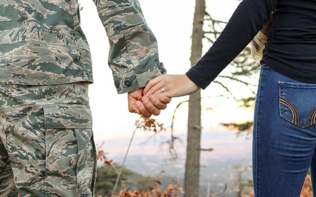 A military man and his wife holding hands, representation of military spouse relocation