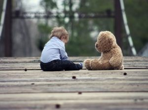 A toddler sitting on the ground with his teddy bear.