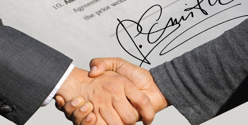 a handshake and a signed contract in the backgorund
