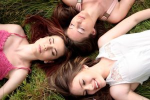 Three girls laying on grass with their eyes closed.