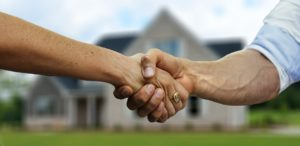 A person shaking hands with a realtor after hiring them to help them find an apartment when moving to Jeddah.