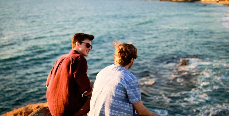 Two friends by the water discussing downsides of friends helping you pack.