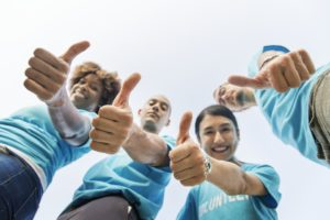 A group of people showing thumbs up.