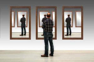 A man looking at himself in three large mirrors.