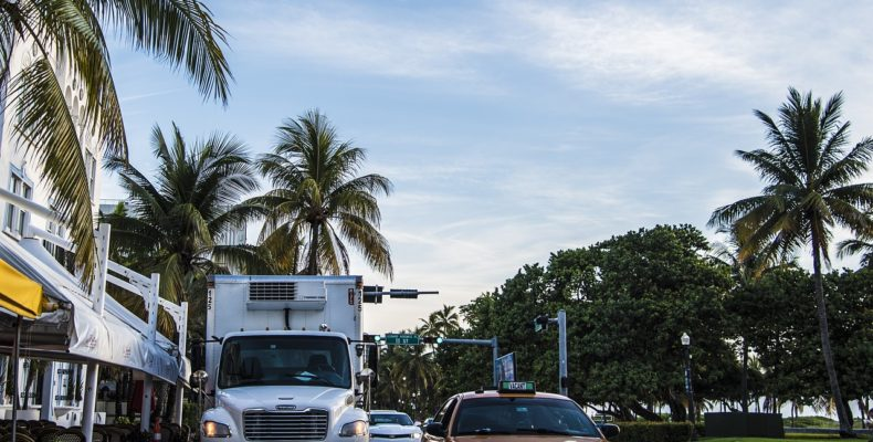 View of the street in Miami, a car and a truck driving.