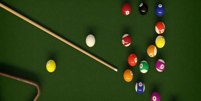 A top-down view of a pool table with a set billiard balls and a cue.