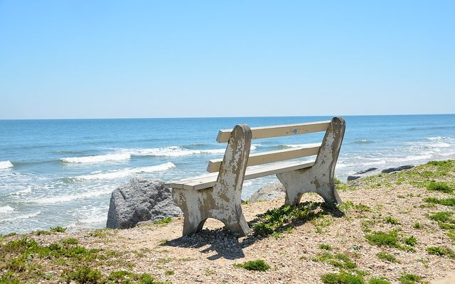 A bench near a beautiful beach, as one of the reasons to relocate to the sunshine state.