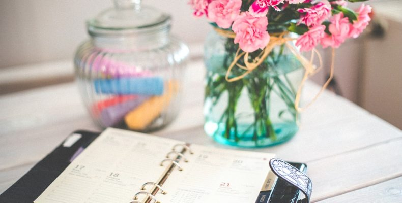 A table, some flowers in a vase and an organizer you can use to organize your local relocation.