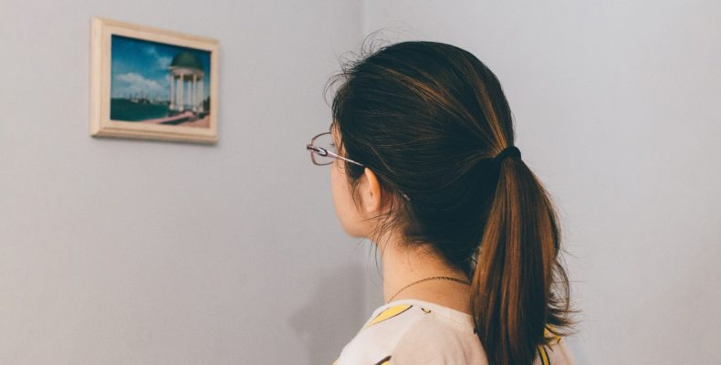 Young woman looking at the frame and thinking about how to properly pack mirrors and pictures for moving.