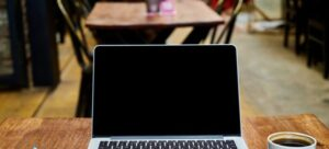 A laptop, notebook, pen, and a cup of coffee on the table.