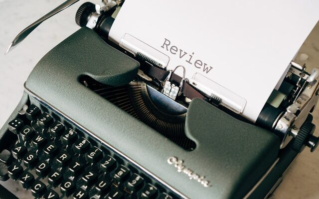 A writing machine that has a paper coming out of it with the word 'review' written on it to signify the importance of moving reviews.