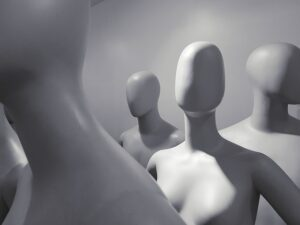 A bunch of faceless mannequins standing next to one another.