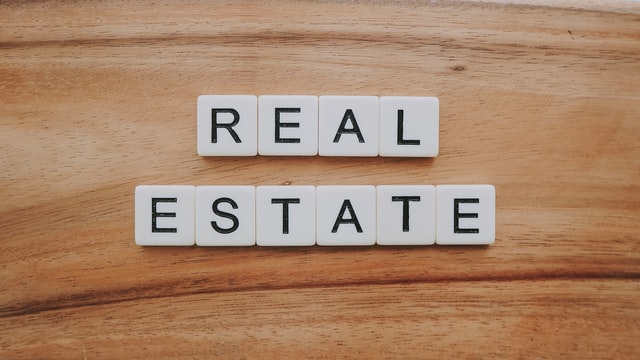 the words real estate written in a game of scrabble