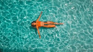 A woman in a colorful bikini chilling in a pool, which is one of the reasons that makes Miami a great place for expats.