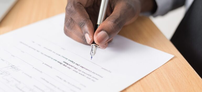 A man signing a contract before leaving New Jersey for a job in Florida.
