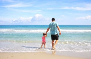 A man walking on the beach with his daughter