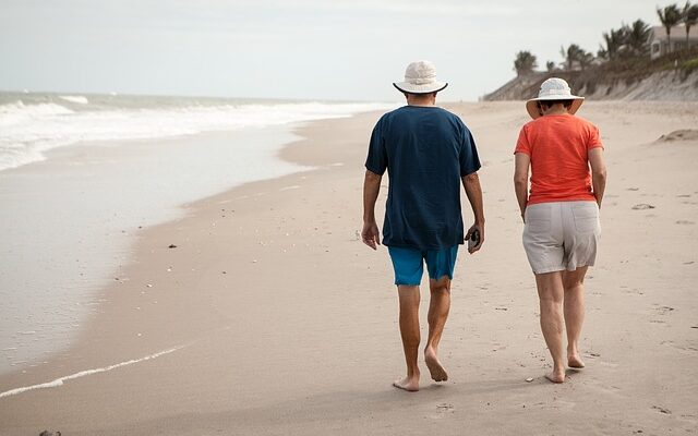 An older couple is walking on the beach, and they are looking for quiet places in Florida retirees will love.