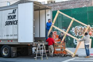 Professional movers loading a moving truck after pacing lamps and chandeliers for a long-distance move.