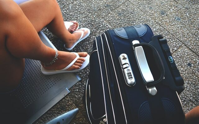 Woman wearing flip flops sitting on a chair next to her luggage