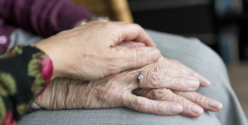 Two elderly women holding hands together.