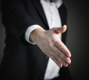 A man in a suit offering a hand for a handshake.