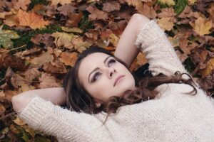 A woman lying on yellow leaves in a park.